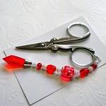 Folding scissors with red beaded scissor weight. B21.