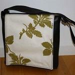 Black Vinyl messenger style handbag with green leaf feature flap