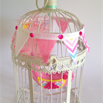 Whimsy bird in vintage cage with bunting. felt bird with real feather tail.