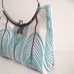 Clutch purse with silver metal frame, turquoise feathers