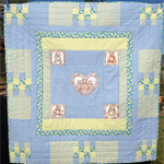 Unique cot quilt featuring teddy bear appliqués  in blues, green and teal .