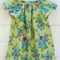 Girls peasant dress with blue and purple flowers on a green background