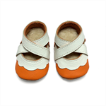 Lambswool lined orange and white soft soled leather baby girl shoes.