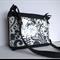 Black bag with front vinyl covered pocket. Long adjustable across body strap.