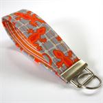 Wrist Key Fob - Pumpkin Orange Geckos on Grey pebble squares.