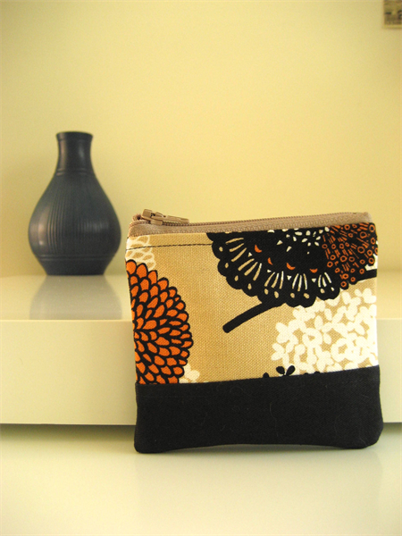 Earthy floral print with orange, black, brown and white pattern lined coin purse