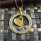 'Kalyke' Free flowing 38mm Silver washer together with a 16mm Gold heart pendant