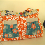 Orange and white handbag with floral pockets and blue, mustard and grey lining