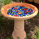 Glass mosaic birdbath with scattered ceramic poppies