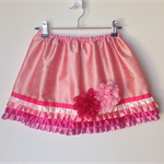 Girls party skirt size 6 pink silk with varying shades of pink satin frills .