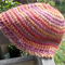 crocheted cloche made from wool/soy yarn.  pink, orange, mauve, camel