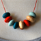 8 bead wooden 'Poly' necklace. Teal,red and mint.