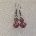 Glass pearl earrings with crystals .