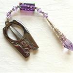Folding scissors with mauve prism and mauve beads.