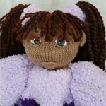 Knitted doll in purple jumpsuit